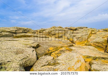 Stony Terrain Of Yellow Color Against The Sky