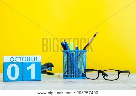 October 1st. Day 1 of month, wooden color calendar on teacher or student table, yellow background . Autumn time. Empty space for text.