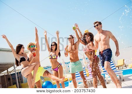 Sunny Pool Disco Party! Splashes Around. Group Of Six Sexy Multi Ethnic Excited Tourists Are Jumping
