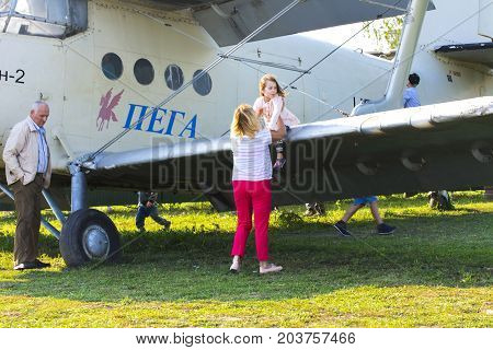 A little girl is sitting on the wing of a private airplane on the airfield. Day of the city. Zhitomir of the year 1133. September 2017 Ukraine.