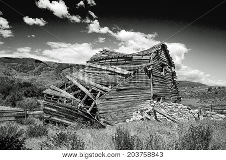 Weathered Old Barn Collapsing Under a Cloudy Sky in Black and White British Columbia Canada