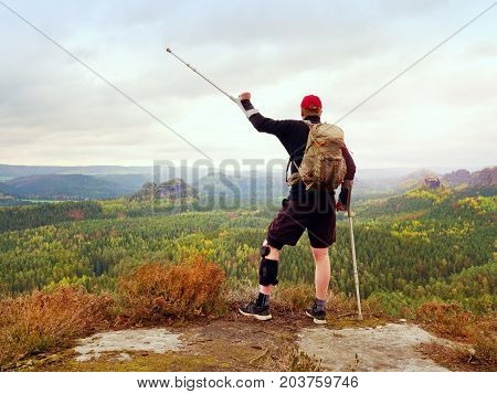 Peak Triumph. Man With Leg In Knee Cages And Crutches For Stabilization And Walk Support.