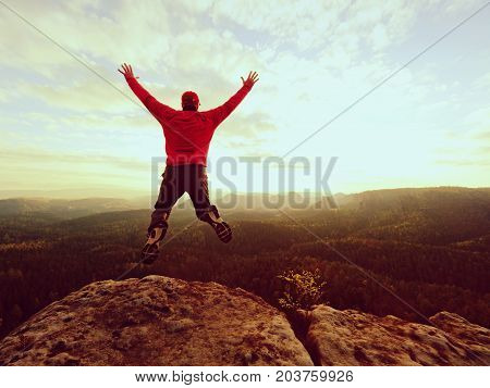 Crazy Man. Hiker Is Jumping  On The Rocky Peak. Wonderful Mood In Rocky Mountains,