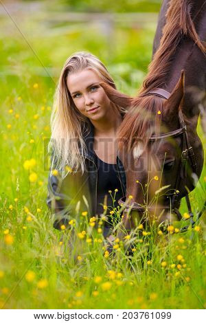 Smiling young woman sitting in the in field with her large arabian horse. Relationship and connection between human and animal.