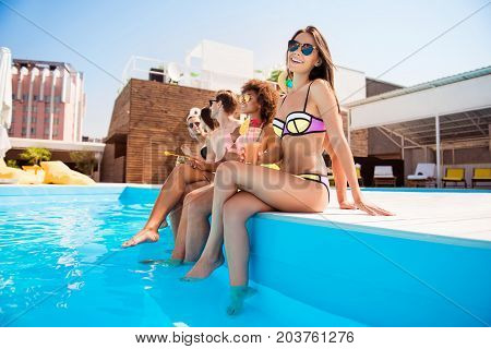 Hot brunette gorgeous girl in sun protective eye wear and colorful bikini drinking juice by the swim pool with legs in blue clean water so attractive ideal enjoying her friends bonding near