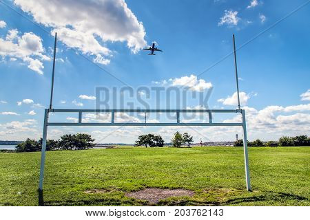An airplane takes off over the football goal posts of a nearby ball park.