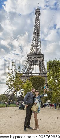 Young happy couple taking a slefie near the Eiffel Tower in Paris.