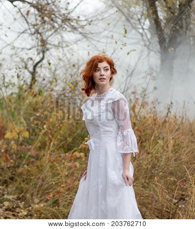 Beautiful young lady with red hair in gorgeous vintage white dress in the forest in the fog. Late autumn cold. Melancholy