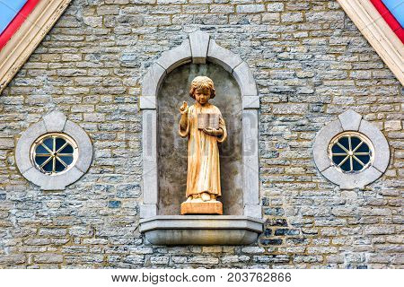 Ile D'Orleans Canada - June 1 2017: Eglise Sainte-Famille church parish with stone architecture golden statue of Jesus Christ boy and small windows poster