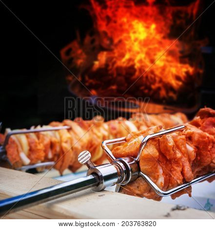 Rotisserie spit with meat bacon and onions before fire