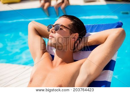 Close up portrait of serene young handsome brunet mature guy in tredy sun glasses tanning near the pool with arms behind the head with closed eyes