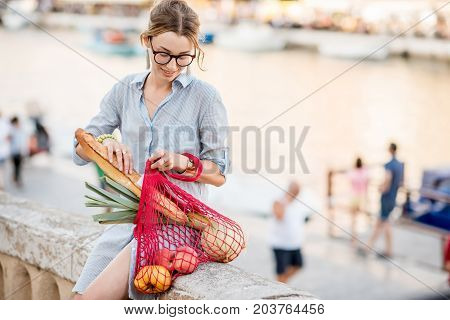Lifestyle portrait of a young woman with mesh bag full of fresh food oudoors in the old city