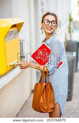 Young woman putting letter to the old yellow mailbox standing with bag and magazine outdoors on the street