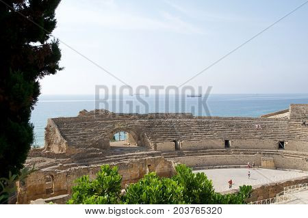 TARRAGONA, SPAIN - AUG 28th, 2017: a panoramic view of the ancient roman amphitheater next to the Mediterranean sea.