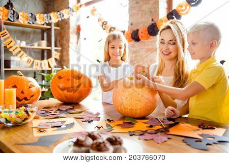 Blonde Cute Family Of Mother And Two Siblings Making A Jackolantern, Boy Is Taking Off The Tail Of P