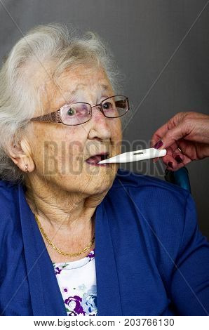 Senior lady having a temperature check with a digital thermometer by a health care worker.