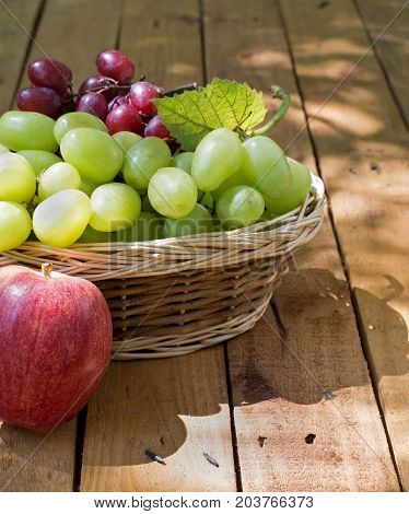 Basket of white and red grapes with an apple on a wooden surface