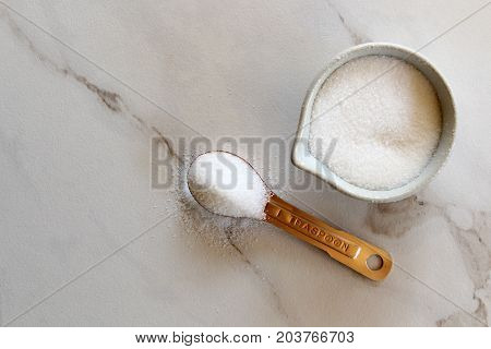 Sugar in copper teaspoon and white pottery measuring cup. White marble copy space.