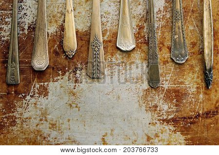 Assorted vintage silverware pieces frame rustic metallic background. Copy space.