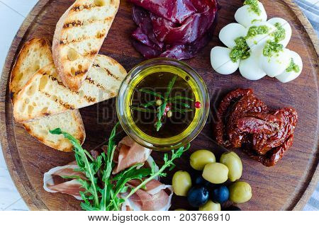 Assortment of spanish tapas or italian antipasti: Prosciutto ham arugula bresaola Mozzarella sun-dried tomatoes olives and toasts on wooden board. Food and drink holidays concept. Top view.
