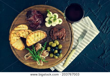 Italian antipasti wine snacks set. Mozzarella cheese Mediterranean olives Prosciutto di Parma bresaola sun-dried tomatoes and toasts on wooden board and red wine in glass. Spanish tapas. Top view.