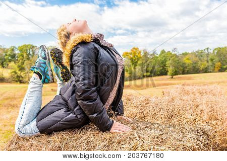 Young woman in downward arch backbend yoga pose on hay roll bale in autumn countryside at farm field