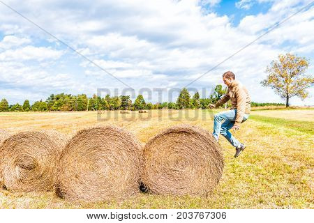 Young Man Jumping In Air Over Hay Roll Bales In A Farm Rural Countryside Field