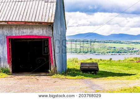 Blue And Red Painted Old Vintage Shed Or Barn With Wooden Wagon Overlooking River In Summer Landscap