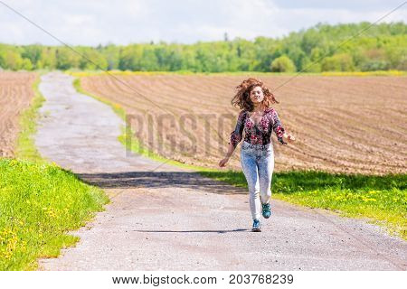 Young Woman Running On Countryside Road By Brown Plowed Fields With Furrows In Summer In Ile D'orlea