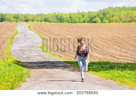 Young Woman Running, Jumping In Air And Smiling On Countryside Dirt Road By Brown Plowed Fields With
