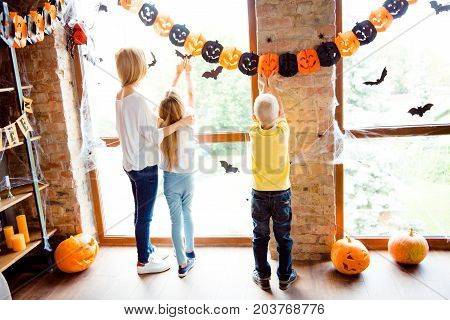 Cute Family Setting The Decor For Party, Mommy With Two Small Blond Kids In Decorated Nice Room At H