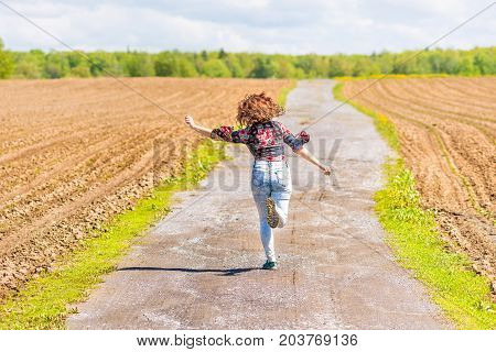 Back Of Young Woman Running, Jumping In Air And Smiling On Dirt Countryside Road By Brown Plowed Fie