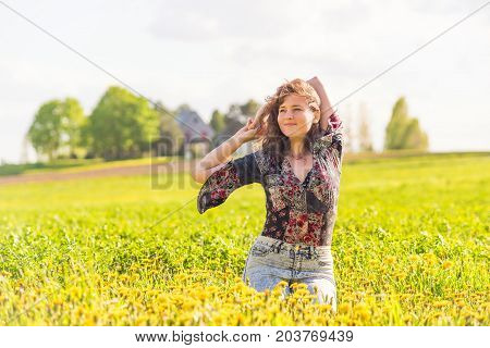 Young Happy Smiling Woman Sitting In Yellow Dandelion Flower Farm Field During Sunset By Countryside