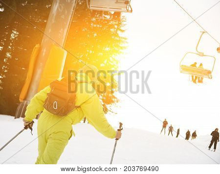 Male skier skiing downhill at ski resort against ski-lift. Male is wearing yellow overalls and backpack. Close-up