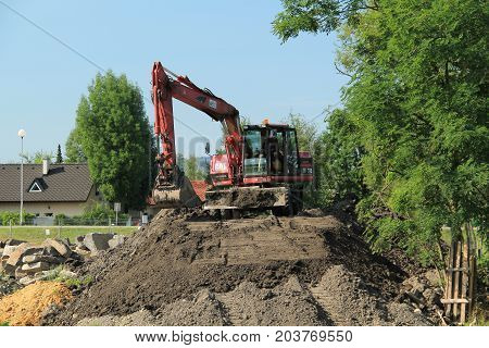 excavator on the mound of soil during the repair of the weir in Frydek-Mistek, Czech Republic, August 24, 2017