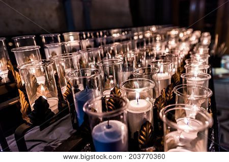 Closeup Side Pattern Of Many White Religious Votive Candles With Yellow Flame In Church Or Cathedral