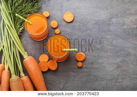 Fresh Carrot Juice In Glasses On Grey Wooden Table
