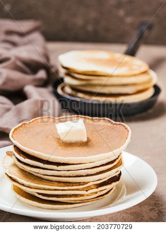 Close up view of homemade pancakes. Stack of pancakes with butter on brown concrete background.