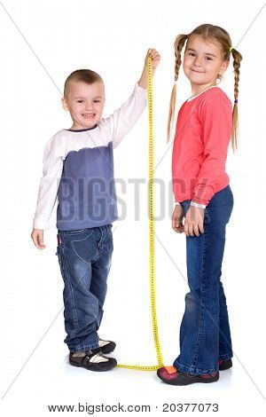 little boy measuring her sister's height