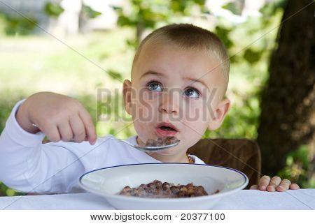 little boy is eating his breakfast