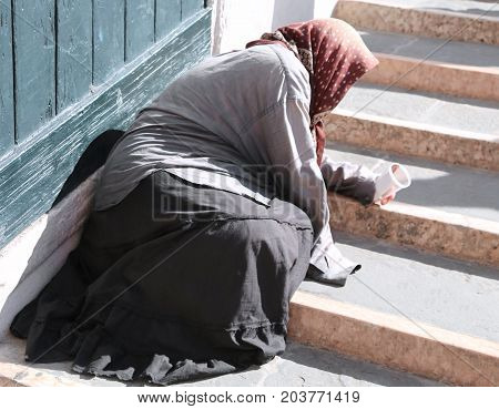Gypsy Woman With Headscarf And Long Skirt Begging People On The