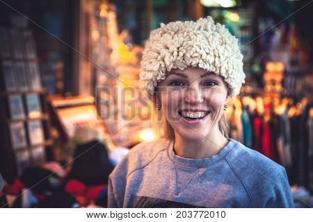 Smiling woman tourist trying on traditional Balkan hat on local souvenir market during her travel holidays