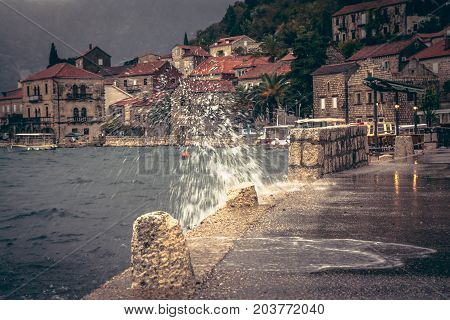 Promenade in rainy overcast day with puddles and splashes in old European city Perast on blurred city background