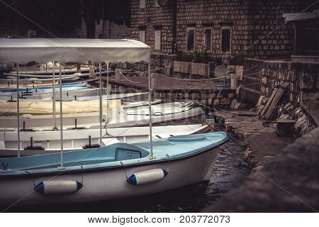Moody old town port with moored  boats in overcast day during raining autumn season in European city promenade with medieval architecture