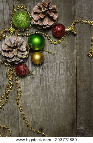 Christmas background with a red golden green christmas balls and fir cones.