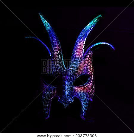 A colorful, scary halloween mask in blues and purples against a black background. The mask is pointy, with a macabre aspect. The mask face is in shadow and would be a great trick or treat costume.