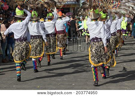 June 17 2017 Pujili Ecuador: indigenous men in traditional wear performing street dance during Corpus Christi festival in the Andean town