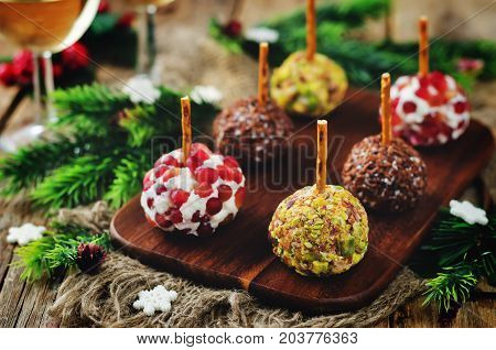Variation of goat cheese balls appetizer with pistachio pomegranate and flax seeds
