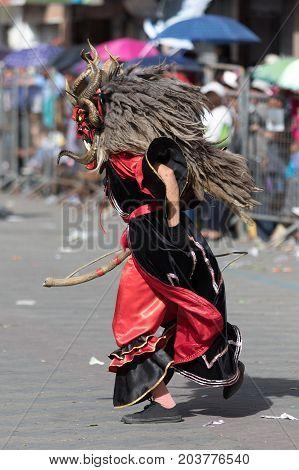 June 17 2017 Pujili Ecuador: closeup of a male dancer with colorful traditional face mask at the Corpus Christi annual parade