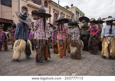 June 25 2017 Cotacachi Ecuador: children wearing sombreros and chaps at the the Inti Raymi celebrations